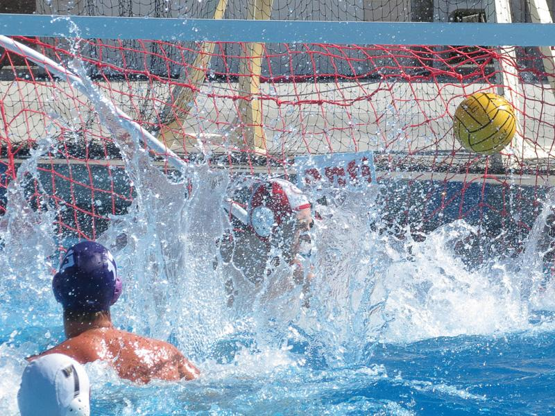 Goal oriented: Hunter Hamaker scores against Chapman Saturday afternoon at the Samuelson Aquatic Center.      Photo by Melina Esparza - Photo Editor