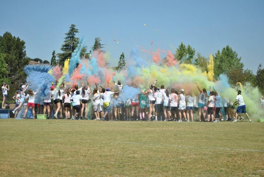 Taste the rainbow: (Top) A final color splashing ended the 5k. (Below) Participants are decorated as they run. Photos by Lauren Rote - Staff Photographer