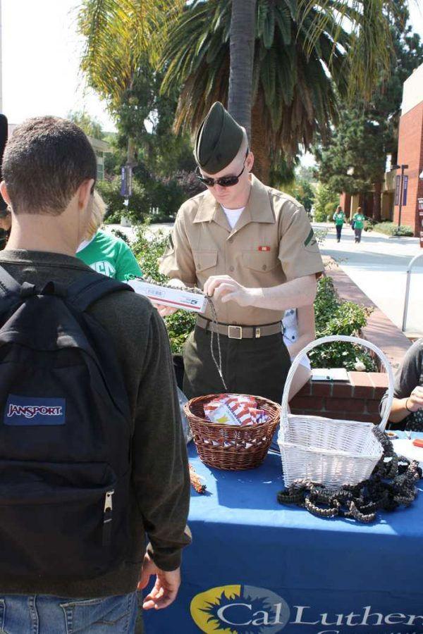 Saluting Service: Cpl. Lance Skidmore helps a CLU student make a paracord bracelet for a soldier.   Photo by Stine Norum - Staff Photographer