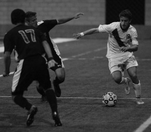 Hugging the line: Junior defender and co-captain Tal Zaiet maneuvering around opposing players. Photo by Andrea Whistler - Staff Photographer