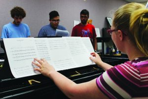 "Aca-Practice: Pianist Kirsten Fuchs organizes her music sheets while her fellow vocalists practrice the club's latest song ""Wrecking Ball"" by Miley Cyrus. Photo by Genesis Rodrigues - Staff Photographer"