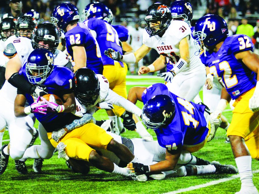 Earning the win: Junior running back Ricky Davis fights for some extra yards. Davis had a season high 167 rushing yards in Saturday night's victory.  Photo by Andrew Whisler - Staff Photographer