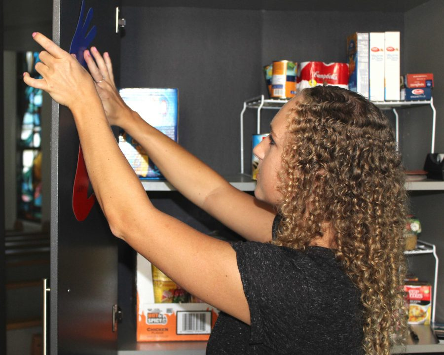 Senior Christy Johnson adds her name to the pantry after adding her food donations. Photo by Andrew Turley - Staff photographer