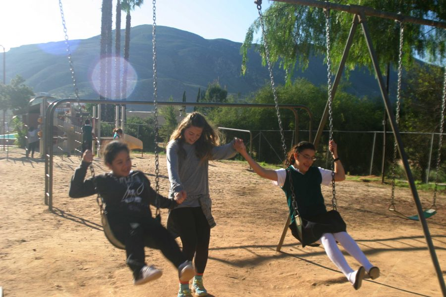 Cal Lutheran student Natalie Elliot (middle) helps a fellow Cal Lutheran student (left) get in sync on the swings with one of Rancho Sordo Mundo's hearing-impaired students during recreation time after breakfast on Monday.  Photo courtesy of Elizabeth Roemisch