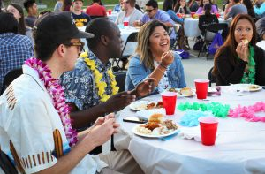 Students Tetteh Canacoo, Paulyn Baens and Trianna Owens enjoy food served at the Hawaiian club's annual Luau.  Photo by Jackie Rodriguez - Staff Photographer