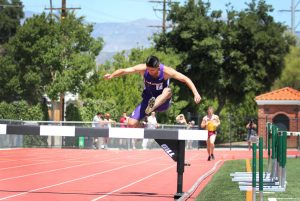 Senior team captain David Avila going over a barrier in the men's 3000-meter steeplechase for Cal Lutheran. Despite facing an injury in the middle of the race, Avila finished the race. Photo by Madi Schmader - Staff Photographer