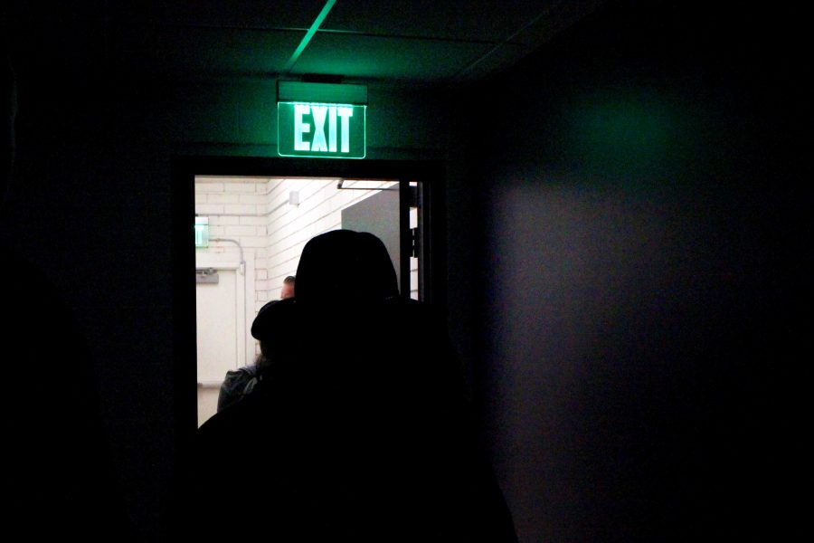 """Andy Hanson leads Cal Lutheran students through the Tunnel of Oppression in the student union. He said, """"When we saw that exit sign, we were able to leave that situation. Others are stuck""""."""