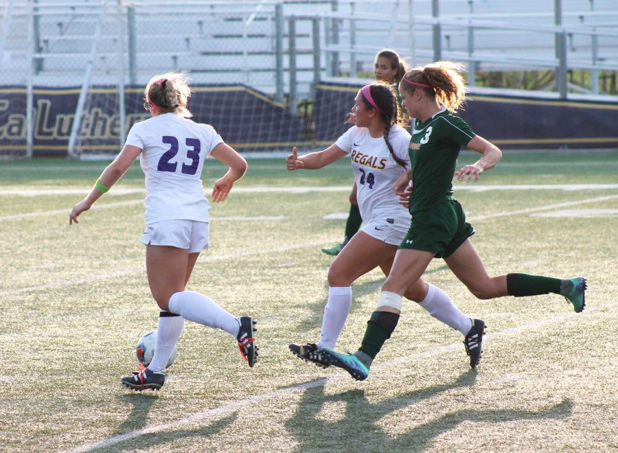 Running past: Julia Kearns and Maddy Griess take the ball and run past La Verne defenders to gain ground for the Regals.  Photo Credit--Kaelani Medina Staff Photographer