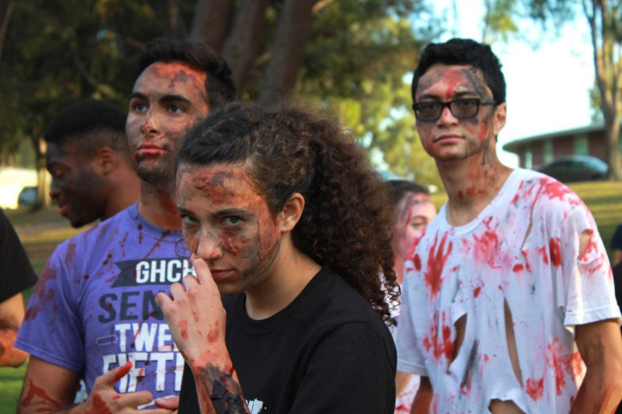 Marathon of the living dead: Sophomore Ramsey Khader, sophomore Alison Yurk and senior Keanu Quick get into their zombie characters complete with bloody make-up prior to the run.