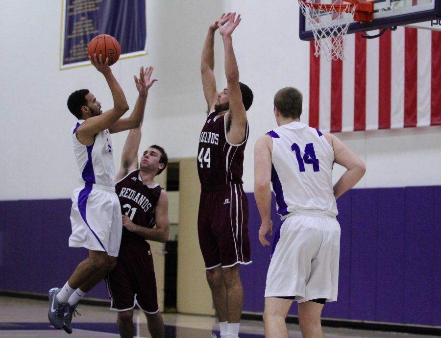 Junior guard #0 Kenneth Moffett goes up for a jump shot and senior center  #14 Jacob Dawe comes up to ensure the two points fall for the Kingsmen.  Staff Photographer--Mary Crocker