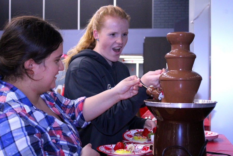 Taylor Trujillo and Brittany Devalk enjoy the chocolate fountain and other treats at the Valentine's Day Bash. Photo by Mary Crocker - Staff Photographer