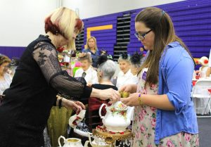 Student Ambassador Tori Lahney (R) helps University Village Activities Director Jayne Austin (L) make tea for the University Village table during the seventh annual Hats and High Tea event intended to raise money for scholarships on March 12 in Gilbert Arena. Photos by Amanda Souza- Staff Photographer