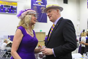 Kim Overton (L) and John Larisey (R) share a conversation by the silent auction tables at the seventh annual Hats and High Tea event intended to raise money for scholarships on March 12 in Gilbert Arena.  Photos by Amanda Souza- Staff Photographer