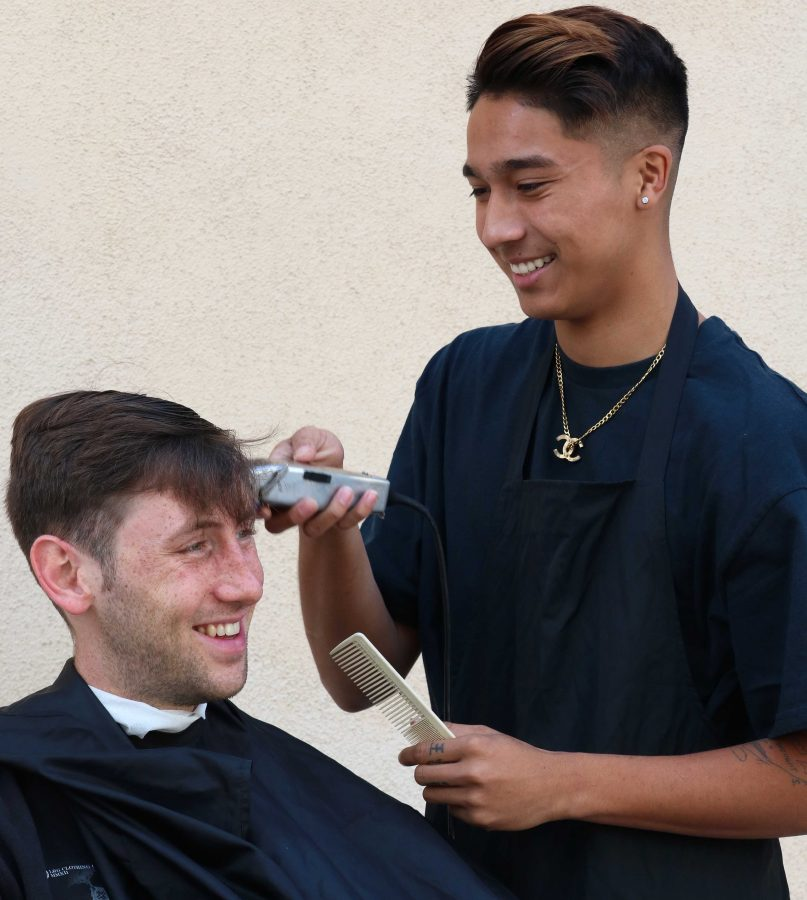"""The hustle: """"I'm busy all the time, it's nice though, I like being busy,"""" Ugale said, cutting senior Brian McElroy's hair. Photo by Inga Parkel - Photojournalist"""