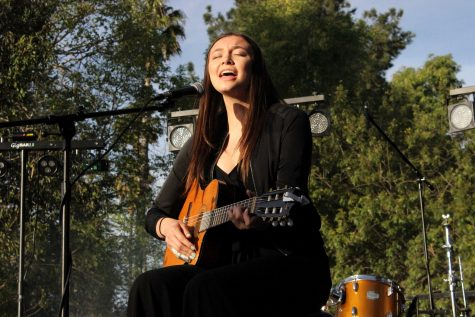 "Cal Lutheran Alumna performed an original song about tragedy and loss in the third annual Sunrise Remembrance Ceremony in her hometown of Las Vegas, Nevada, the site of the Route 91 mass shooting. Pictured: Poggione performs her original song ""Thinking About You,"" in Kingsmen Park."