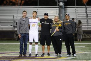 Senior defender Alex Cortez wore his white jersey for the last time as a Kingsmen alongside his family and Head Coach Miguel Ruiz. Photo by Ally Gaskill - Photojournalist
