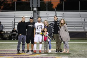 Senior Jared Pischke's family support him during his last home game as a Kingsmen, alongside head coach Miguel Ruiz. Photo by Ally Gaskill - Photojournalist