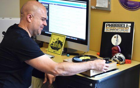 Tocadiscos: Carlos Velasquez le sonríe al tocadiscos que representa su pasión por la música, mientras mantiene una energía positiva en la oficina. Foto por Allison Gaskill- Fotoperiodista