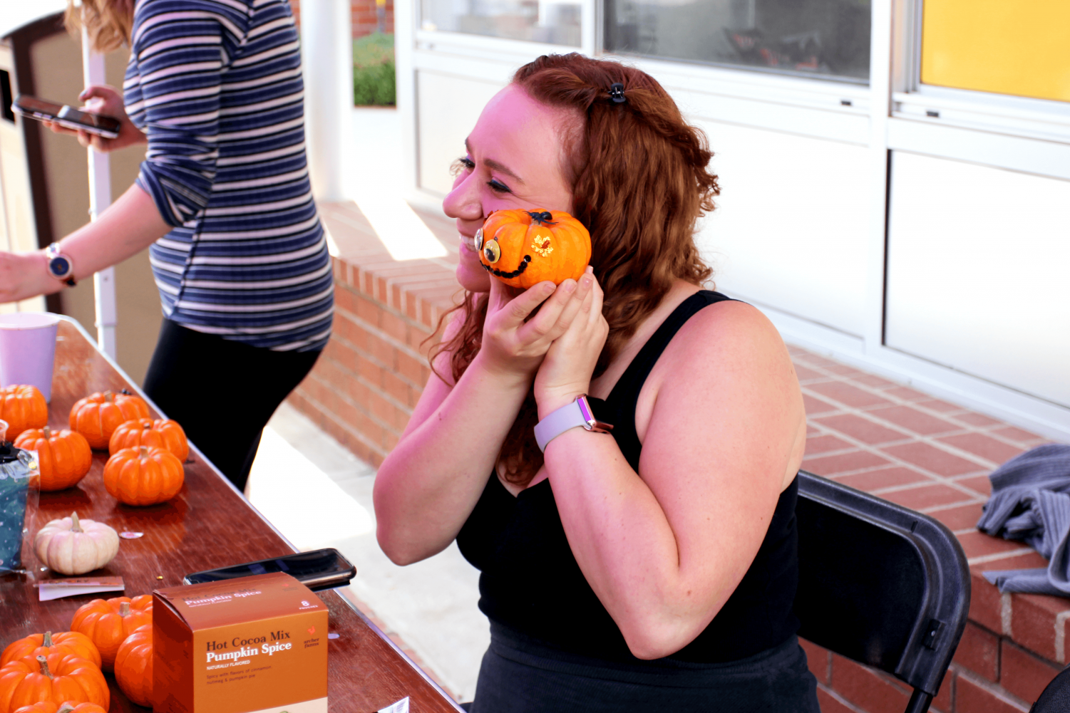 Melissa Tobey, junior, poses with her decorated pumpkin on the Spine on Tuesday Oct. 15.