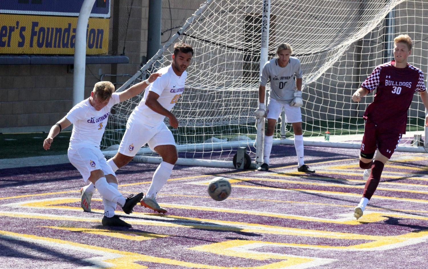 First-year forward Matt Myers (left) and junior defender Lucca Rodrigues (middle) work to kick the ball out of the defensive zone, assisting sophomore goalkeeper Owen Ebner (right).