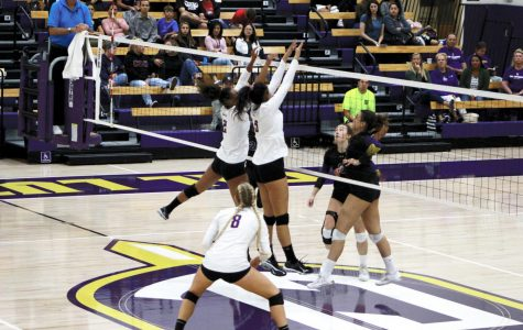 Junior outside hitter Sarah Hein (left) and first-year middle blocker Christina Williams (right) try to block the ball from the Whittier Poets on Oct. 5.