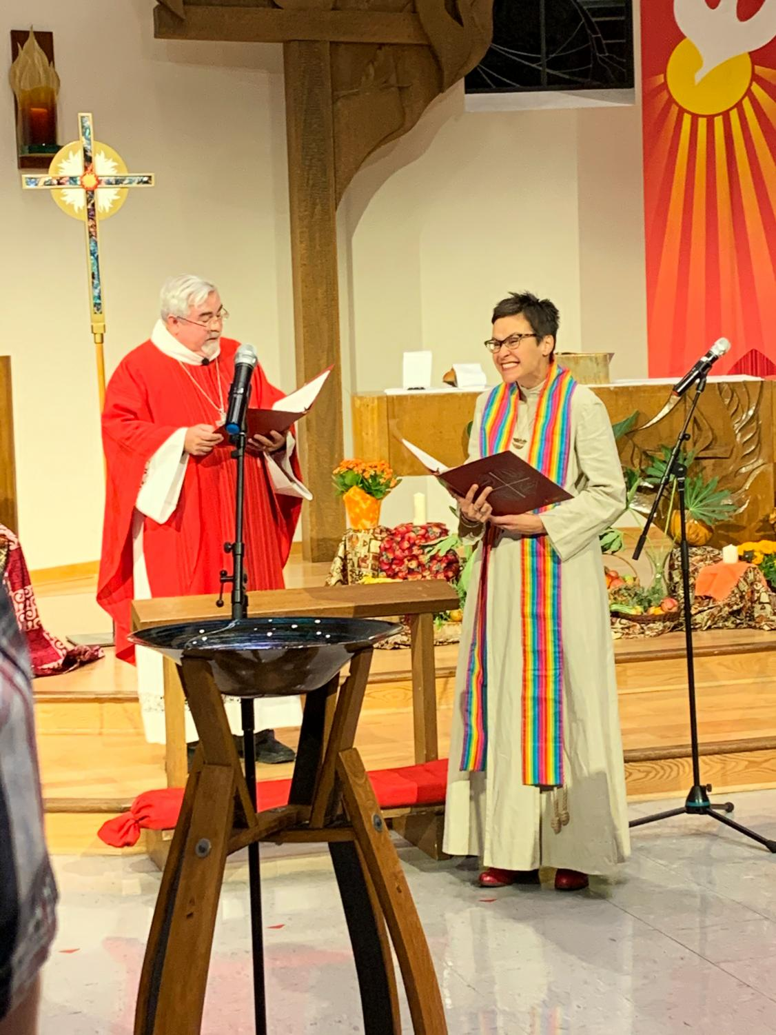 Associate professor Colleen Windham-Hughes smiles at the crowd as Bishop Guy Erwin reads the communion text on Friday Oct. 25.