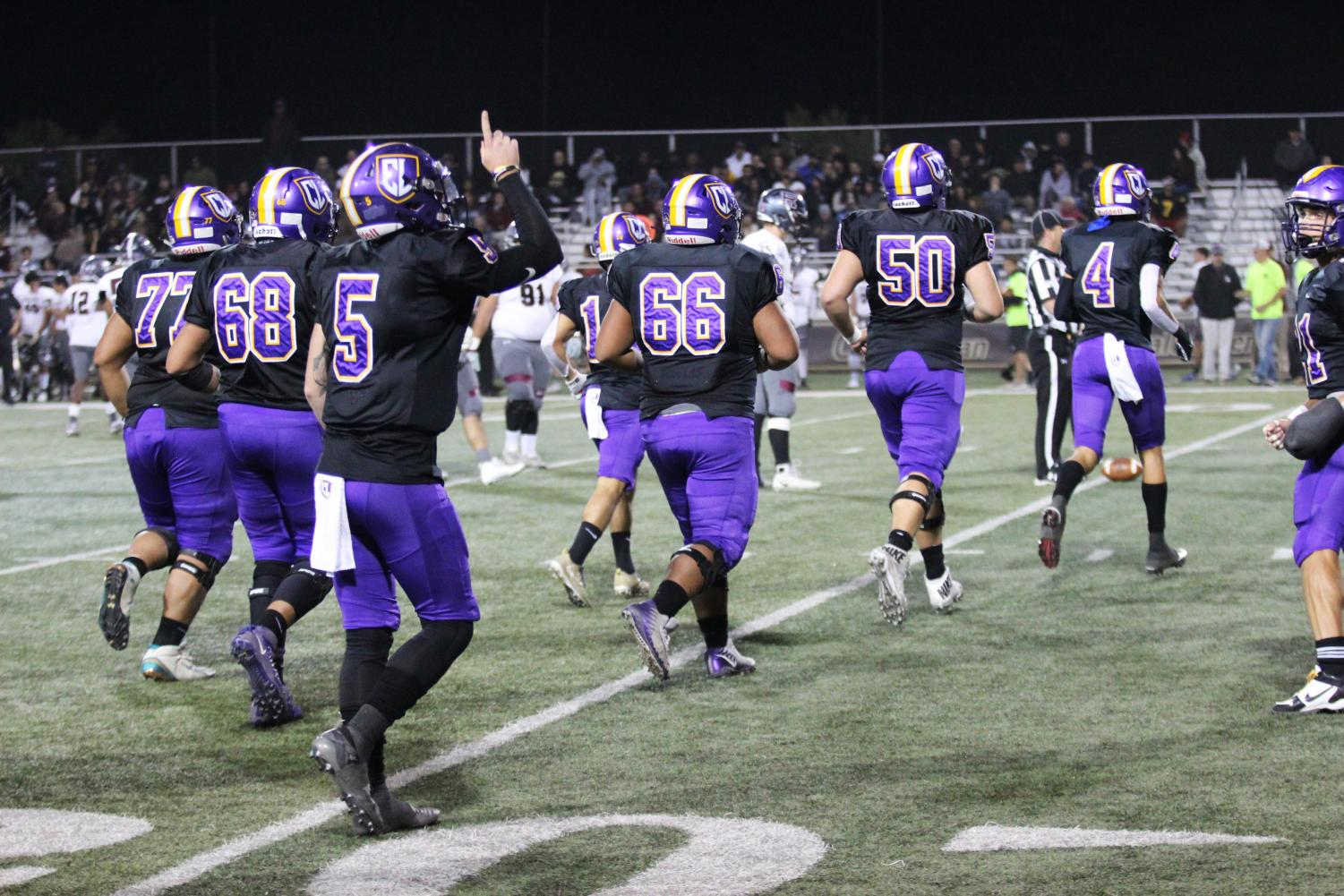 The Kingsmen offensive line runs on the field as senior quarterback Cesar De Leon points to the sky with only two games left in the season.