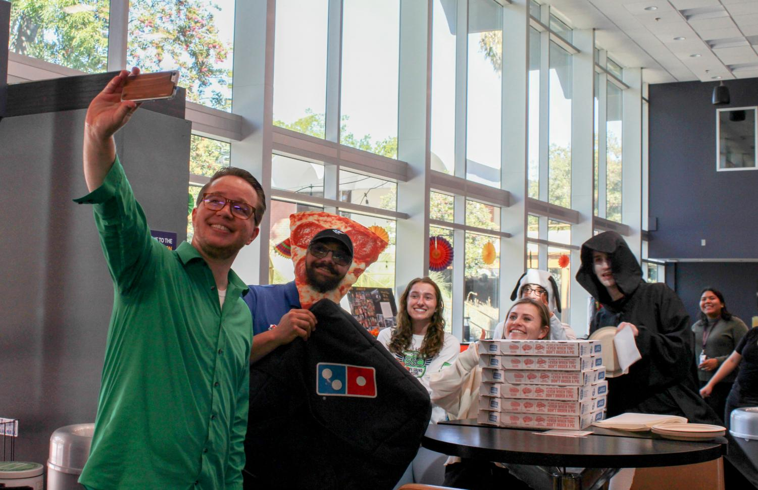 Andrew Hanson, senior coordinator for Residence Life and Student Conduct, takes a selfie after the Domino's delivery man dropped off boxes of pizza while dressed as a pizza.