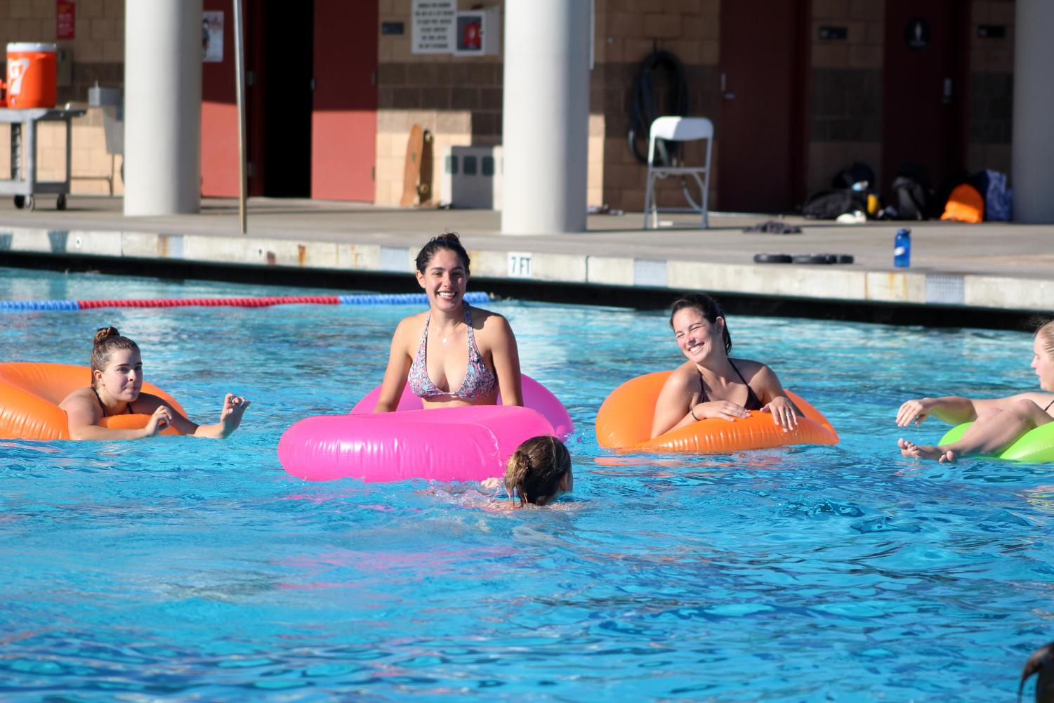 Senior Morgan Snyder (left) laughs with her team as they watch other participants get ready to shoot at intramural sport's innertube water polo tournament.