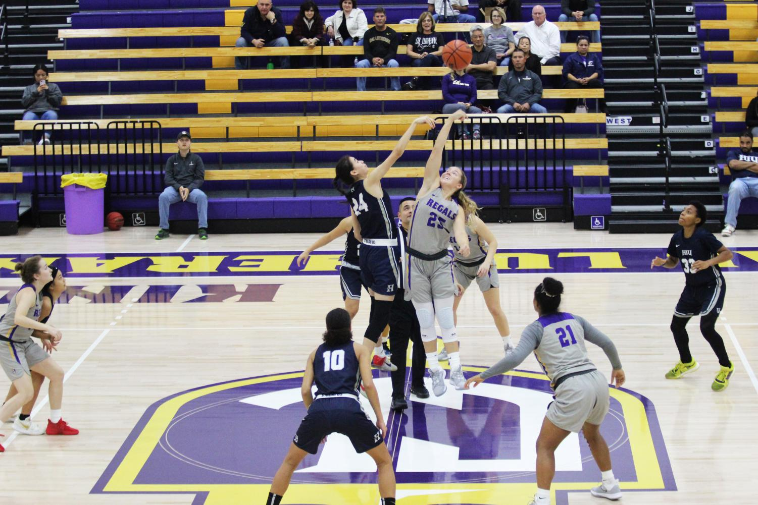 Regals sophomore forward Cameron Mallory gets possession of the ball after tip off against Hope International first-year forward Mia Heidt on Wednesday, Nov. 6.