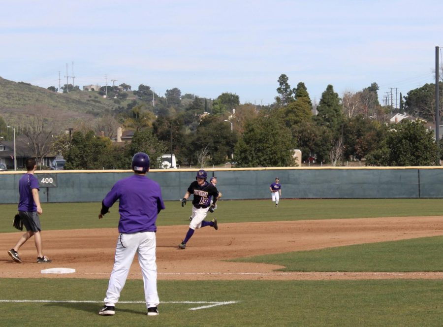 Coaches usher Kingsmen through the bases during the alumni game in Jan. 2020.