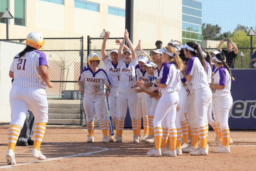 First-year Ariana Mendoza (#21) runs to her team as they cheer her on after hitting a home run.