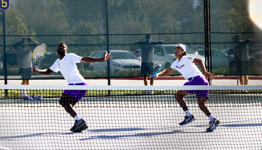 In accordance with SCIAC's prohibition of in-person spectators this season, the bleachers are empty and some sports personnel are seen standing outside of the exterior fencing around the tennis courts at Cal Lutheran during a doubles match on Feb. 27. Most Cal Lutheran competitions are available via live stream on CLUSports.com.
