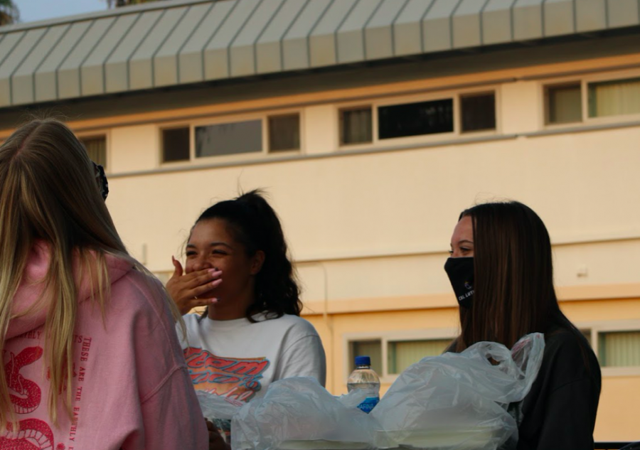 Students enjoy takeout in front of Thompson and Pederson, some of the first-year residence halls at Cal Lutheran.