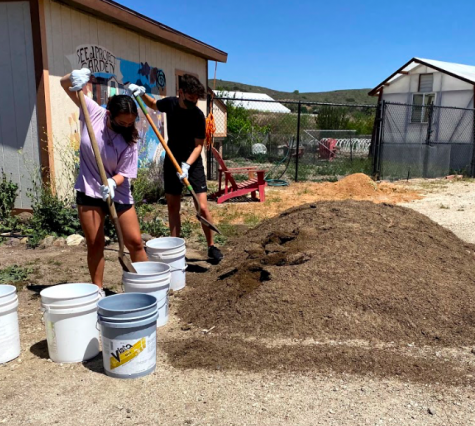 Asia Kison and Amanda Lewin shovel soil into buckets to distribute the soil evenly into the composting bin during the SEEd Garden volunteer event.