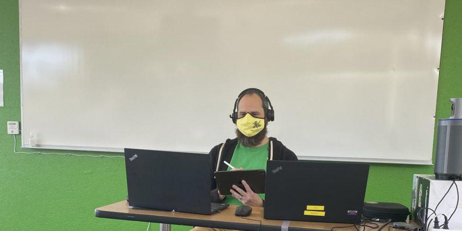 El Dr. Gagliardo está interactuando tanto con sus estudiantes virtuales como con los estudiantes en persona a través de las pantallas mostradas.