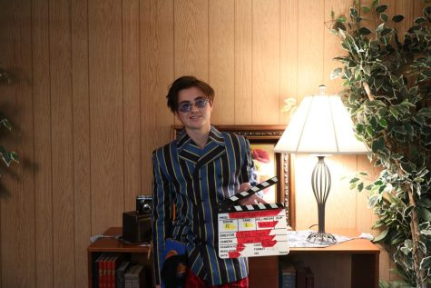 Reed Sharp holds up a clapperboard to prepare for the upcoming scene.