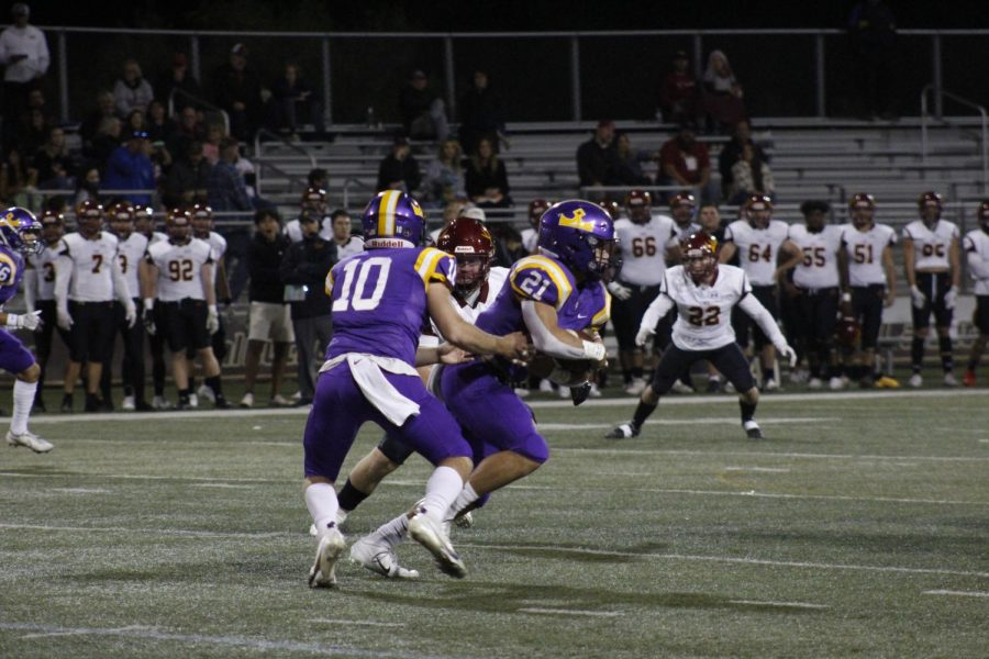 Quarterback Nick Lasher hands the ball of to Jackson Taylor as the Kingsmen look to score.